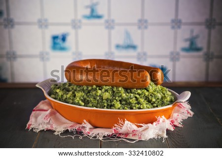 A rustic kitchen with a dish with 'Boerenkool met worst' or kale with smoked sausage, a traditional Dutch meal. With typical Dutch Delft blue tiles on the wall in the background. - stock photo