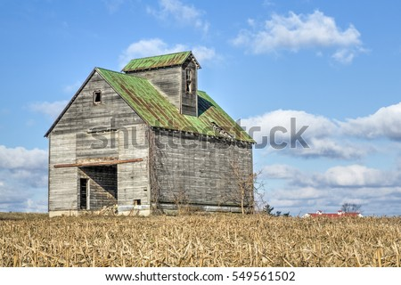 A rustic old barn stands dramatically against a cloudy blue sky in a rural Ohio cornfield.