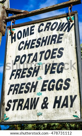 A rustic sign outside a farm selling various produce.
