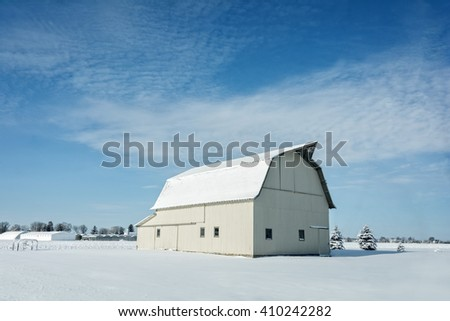 A rustic, white Ohio barn covered in fresh snow with a bright blue sky background.