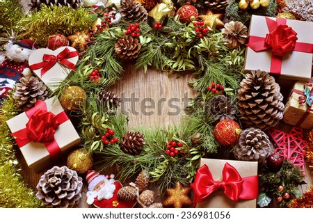 a rustic wooden table full of gifts, and christmas ornaments, such as a natural wreath with branches, berries and pine cones, or christmas balls and stars  - stock photo