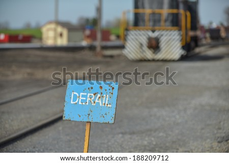 A rusting derail sign in a working train yard with a locomotive in the background