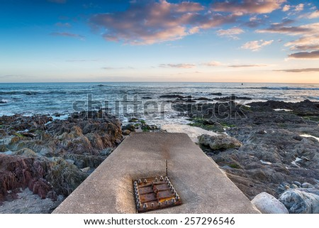 A rusting iron manhole cover on a concrete jetty - stock photo