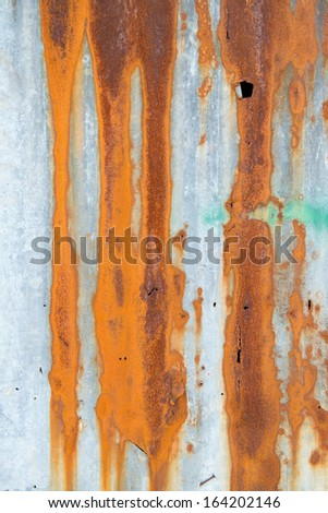 A rusty corrugated iron metal fence close up