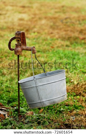 A rusty faucet outside in the yard with a galvanized tin bucket hanging from it - stock photo