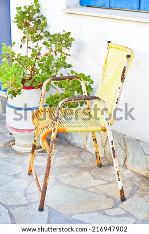 A rusty old garden chair in a courtyard - stock photo