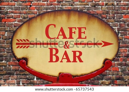A rusty old retro arrow sign with the text Cafe and Bar - stock photo