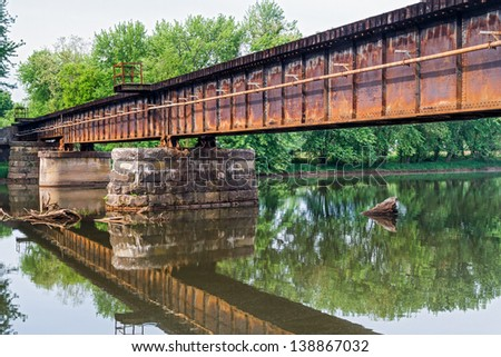 A rusty railroad bridge spans Middle Island Creek in St. Mary's, West Virginia. - stock photo