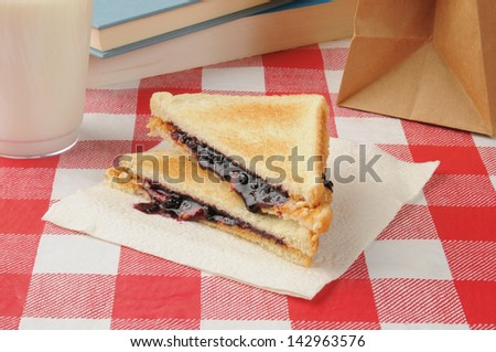 A sack lunch peanut butter and jelly sandwich with a glass of milk - stock photo