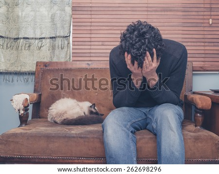 A sad and depressed young man is sitting on a sofa with a cat and his head buried in his hands - stock photo