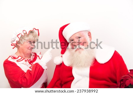 A sad and grumpy Santa being scolded by Mrs Claus. - stock photo