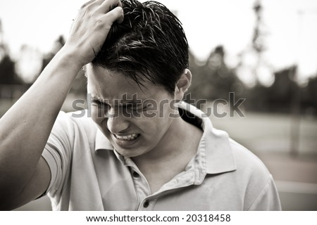 A sad and stressed young asian male in black and white - stock photo