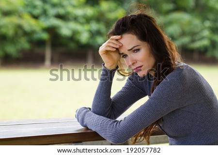 A sad and worried woman sitting down alone outdoors - stock photo