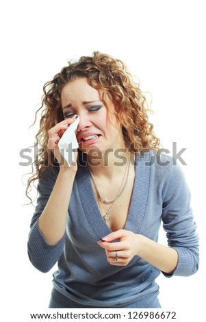 A sad beautiful woman crying or sneezing over white background - stock photo