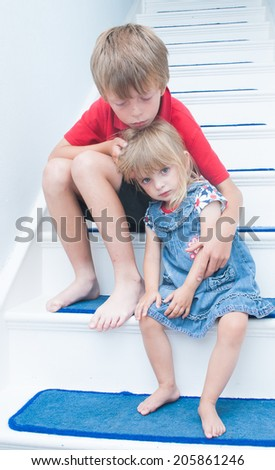 A sad brother and sister sitting on the stairs of the family home.