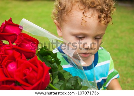 a sad child with a bouquet of red roses - stock photo