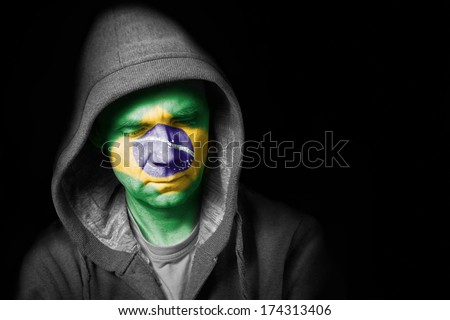 A sad expression on the face of a football fan with their face painted with the Brazilian flag. - stock photo