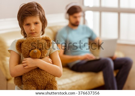 A sad little boy looking in camera and hugging a teddy bear, in the background his father using a laptop while sitting on a sofa without paying attention to his son. - stock photo