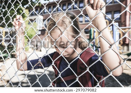 A sad little girl at school playground with fence on front of is fence.