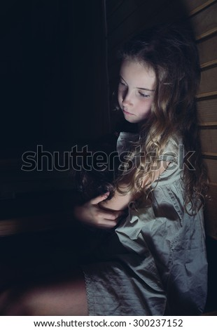 A sad little girl hugging a doll at home - stock photo