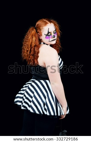 A sad little red-headed clown.  Shot on black background. - stock photo