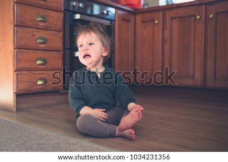 A sad little toddler is sitting on the kitchen floor at home