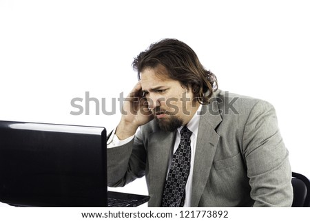 A sad looking business man isolated on white with a laptop
