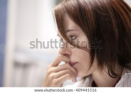 A sad or anxious woman with her hand on her face. - stock photo