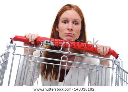 A sad shopping girl hanging behind her empty shopping cart.