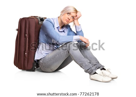 A sad tourist girl seated next to a suitcase isolated on white background - stock photo