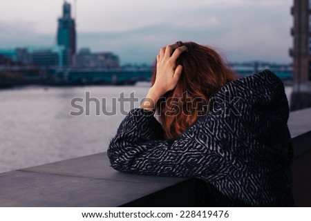 A sad woman is standing by a river in the city and is holding her head - stock photo