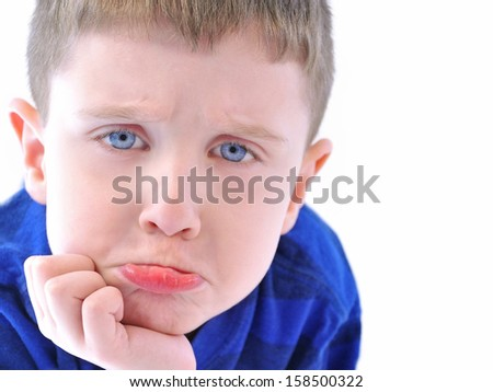 A sad young boy is upset on an isolated white background with a blue shirt for a parenting or problem concept. - stock photo