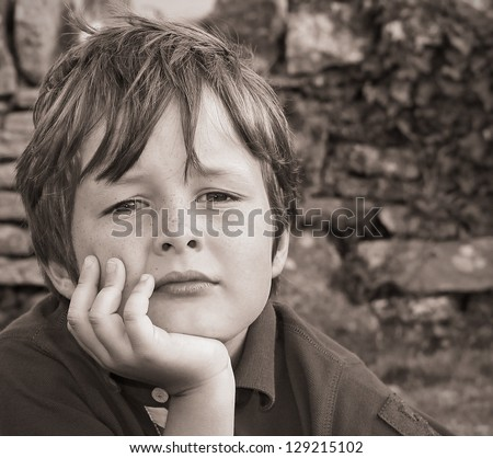 A sad, young boy looking into the camera - stock photo