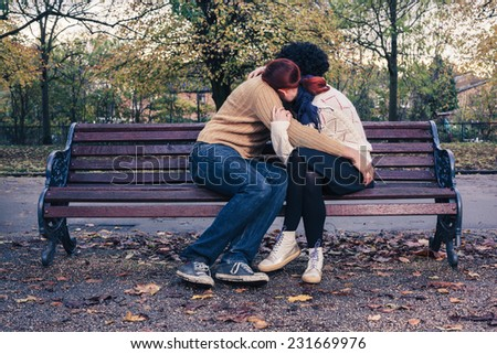 A sad young couple is embracing on a park bench in autumn - stock photo