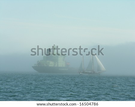 A sail boat, and container ship in the fog, at Halifax harbor, Atlantic Canada. - stock photo