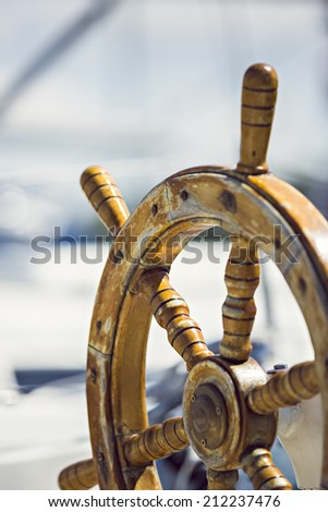 a sailboat, antique wood steering wheel