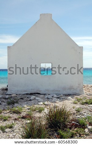 A sailboat framed in White Slave Hut window in Bonaire. - stock photo