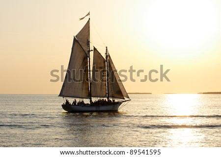 A sailboat full of people is sailing into the sunset before a yellow sky. - stock photo