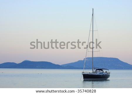 A sailboat is waiting in evening stillness - stock photo