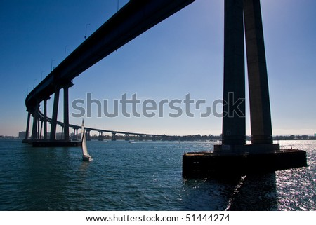 A sailboat under the San Diego - Coronado Bridge. - stock photo
