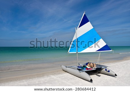 A Sailboat with a Blue and White Sail raised setting on the Beach - stock photo