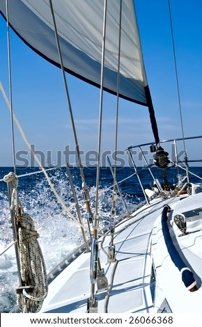 A sailboat with reefed jib is hard on the wind, heading towards the open ocean creating spray.