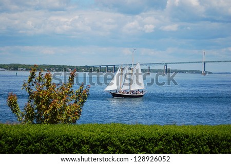 a sailing boat is sailing by newport bridge, rhode island - stock photo