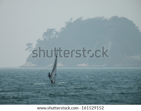 A sailing boat with someone in the middle of the ocean. - stock photo