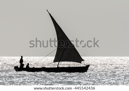 a sailing dhow silhouetted against the sunlight and ocean water with crew