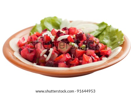 A salad of cooked vegetables on the ceramic plate. Isolated on white