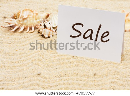 A sale card with sea shells on a sand background, vacation sale - stock photo