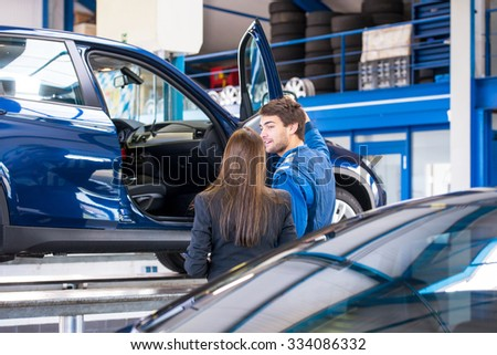 A sales mechanic shows the vehicle he has been working on to a business woman, who is interested in buying it at a used car dealership garage - stock photo