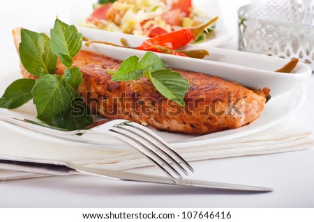 A salmon is fried with a basil and tomato
