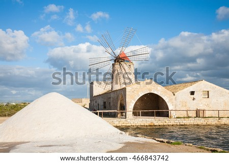 A salt pan windmill and heap of sea salt near Trapani in western Sicily, italy